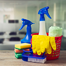 A bucket of cleaning supplies and spray bottles