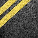 A closeup of black asphalt with yellow road stripes