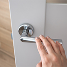 A hand pulls down a silver level-style door handle.