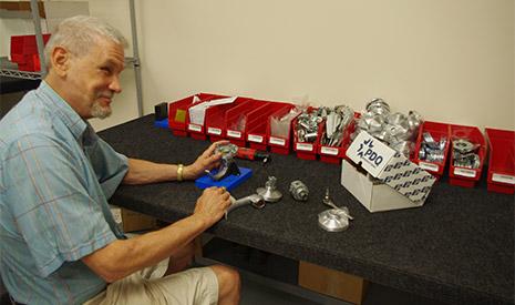 Man in light blue shirt sitting at a table assembling door hardware