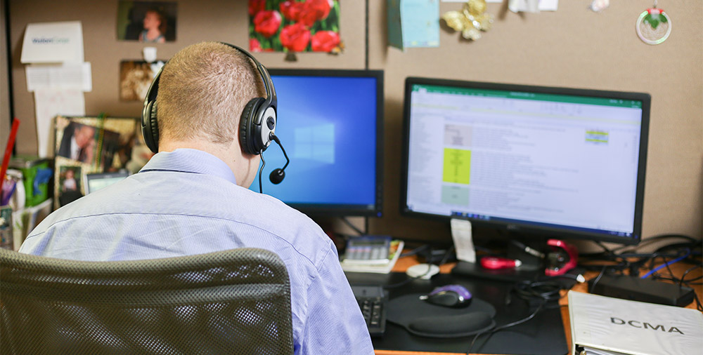 A man in a button down shirt with his back to the camera types on a computer.
